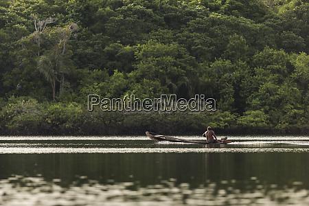 mann in einem hoelzernen motorisierten kanu