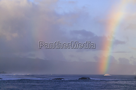 vibrant rainbow offshore pacific storm waves