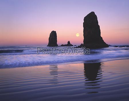 usa oregon cannon beach moonset between