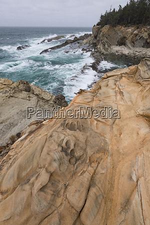 usa surf breaking on shoreline rock