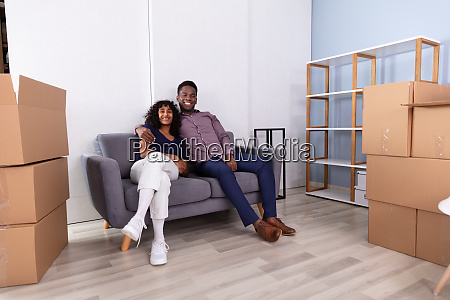 couple sitting on couch inside their