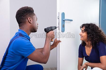 technician fixing the door lock