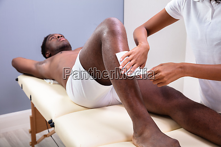 therapist waxing mans leg