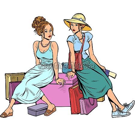 zwei freundinnen sitzen auf dem einkaufsbummel