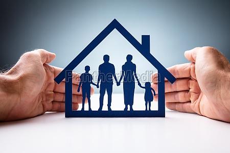 geschaeftsmann schuetzt familienhaus