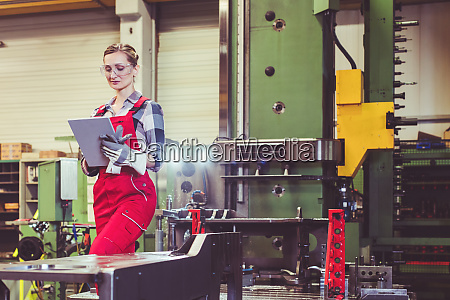 arbeiterin mit tablet computer vor dermaschine