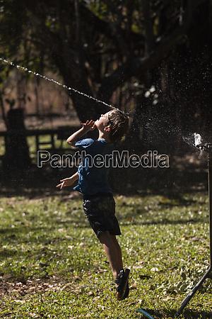 unbekuemmerter junge springt in sprinkler im