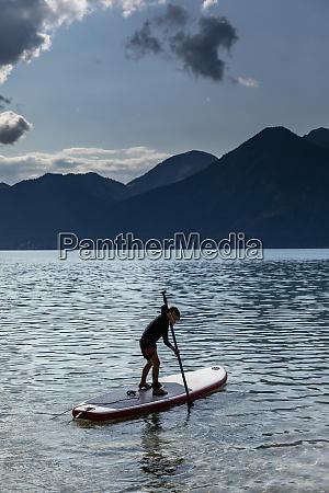 boy paddleboarding auf sonnigem idyllischem see