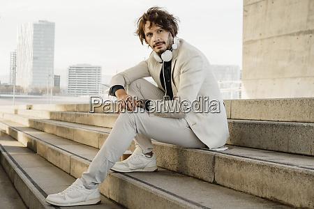 portrait of businessman with headphones sitting