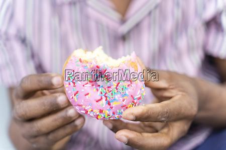 junger mann isst donut