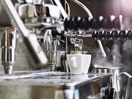two espresso cups getting filled in