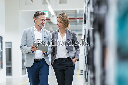 businesswoman and businessman with tablet walking