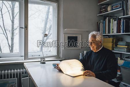 senior mann mit leuchtendem buch auf