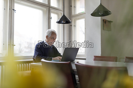 senior mann mit laptop auf dem