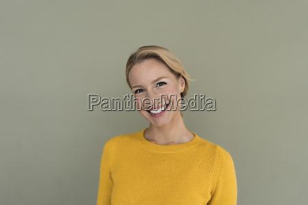 portrait ov laechelnde blonde frau traegt