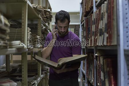man on the phone among bookshelves