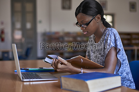 young student with laptop reading a