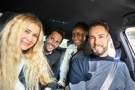 gluecklicher freund sitzt im auto und
