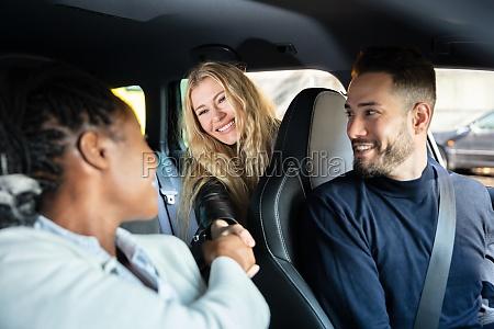 weibliche freunde schuetteln haende im auto