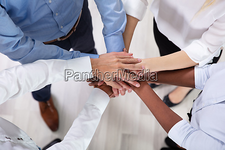 multiracial businesspeople stacking haende uebereinander