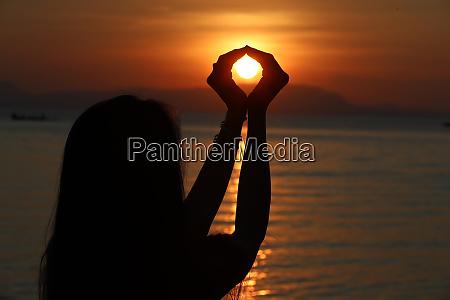 silhouette einer frau die bei sonnenuntergang