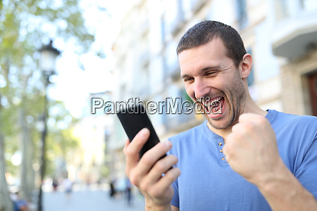 excited man celebrating good news checking