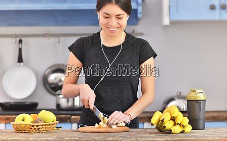 junge frau bereitet proteinshake am tisch