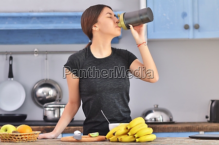 young woman drinking protein shake near