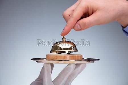 person hand ringing service glocke halten