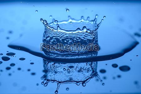wasser spritzt auf glas auf blauem