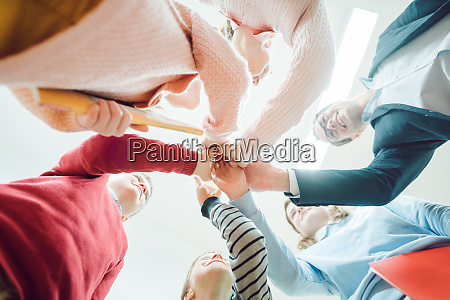 students and teacher stacking hands as