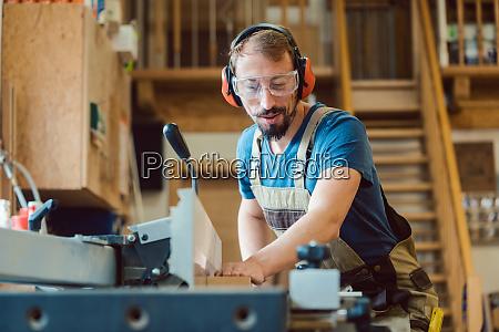 carpenter working at the circular cutter