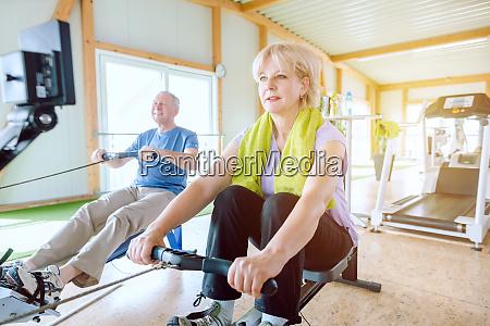seniorenpaar im fitnessstudio auf einem rudergeraet