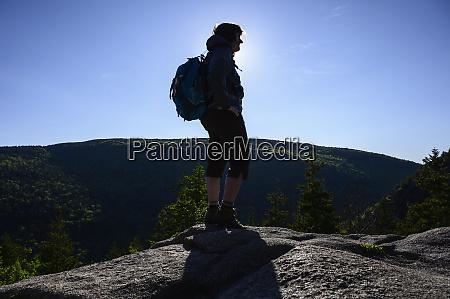 silhouette of hiker on rock