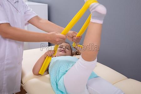 physiotherapeut sanft helfen maedchen strecken ihr