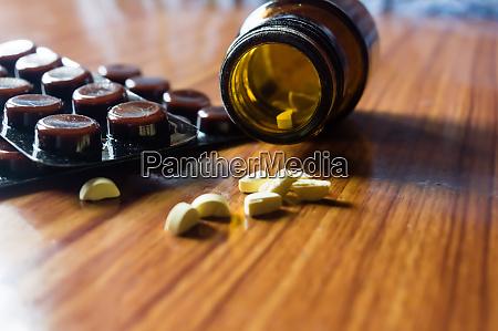 nahaufnahme offene transparente glasflasche mit medikamentenpillen