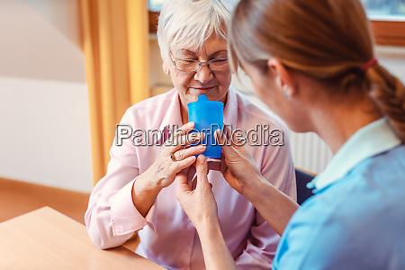 betreuer in der seniorin hilft ihr