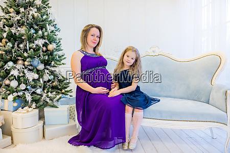 schoene schwangere frau in ultraviolettem kleid