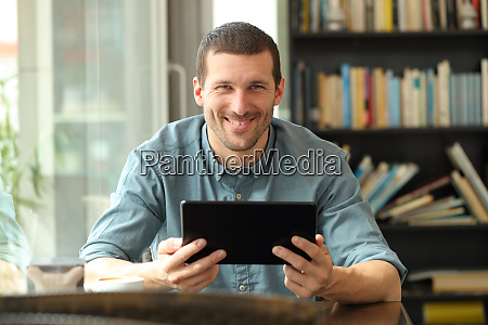 happy man holding tablet looking at