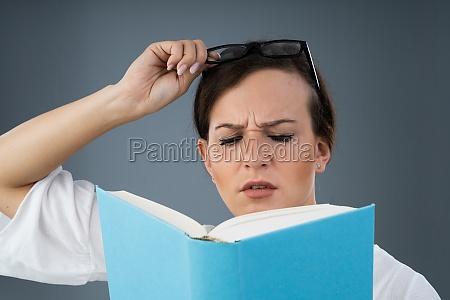 junge frau versucht buch zu lesen