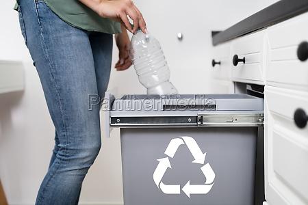 frau wirft plastikflasche in recycling behaelter