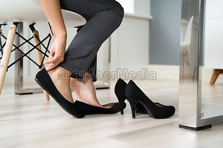 geschaeftsfrau wechselt schuhe im buero