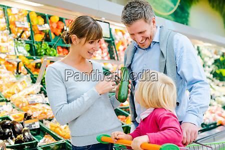 familie kauft obst und gemuese im