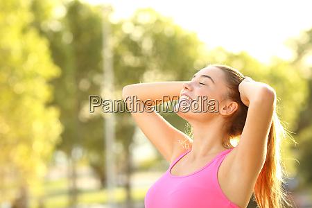 glueckliche sportlerin atmet frische luft in