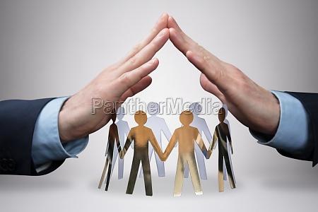 handschutz von geschaeftsleuten fuer papierausschnitte