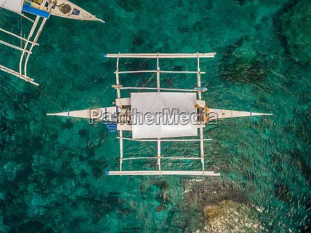 luftaufnahme von weissem boot mit auslegern