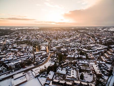 luftaufnahme des schneestadtbildes bei malerischem sonnenuntergang