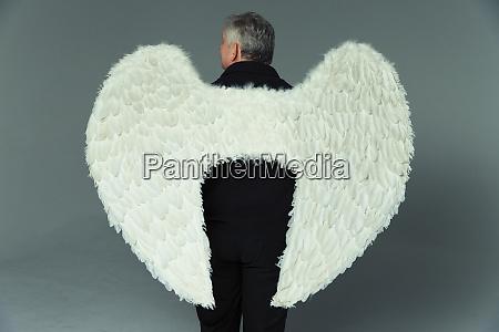 heiterer mann traegt engelsfluegel