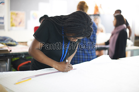 focused female fashion designer drawing sewing