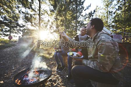 glueckliche freunde essen auf sonnigem campingplatz